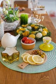 Украшения для пасхального стола. раскрашенные в желтый и зеленый цвет яйца в венке из травы с закусками: помидорами, маслинами и дольками лимона.