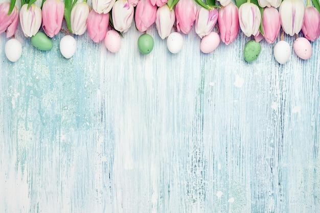 Пасхальный стол. декоративные пасхальные яйца и розовые тюльпаны граничат на деревянном столе. праздничная открытка