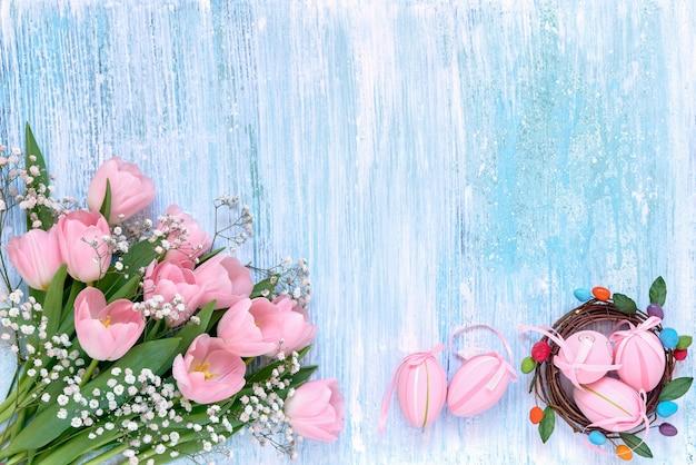 Пасхальный стол. розовые тюльпаны и пасхальные яйца на синем столе. копирование пространства, вид сверху.