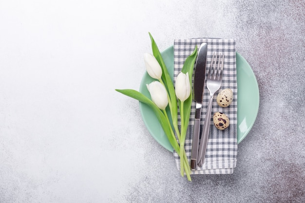 Easter table setting. empty mint and white plates, linen napkin, white tulips and quail eggs on stone background - image