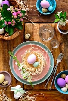 Сервировка пасхального стола, идея домашнего декора праздничного стола, плоская композиция со столовыми приборами, пасхальными яйцами и живыми цветами