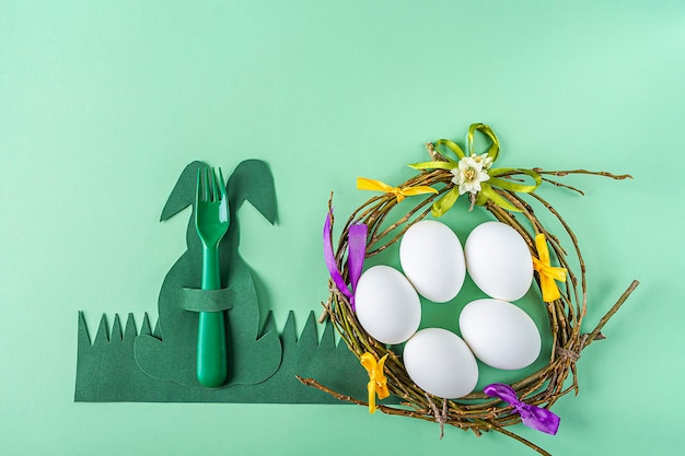 Easter table setting. homemade craft nest of twigs and colorful ribbons with white eggs and creative cutlery holder in form of green bunny on green surface. diy and kid's creativity.