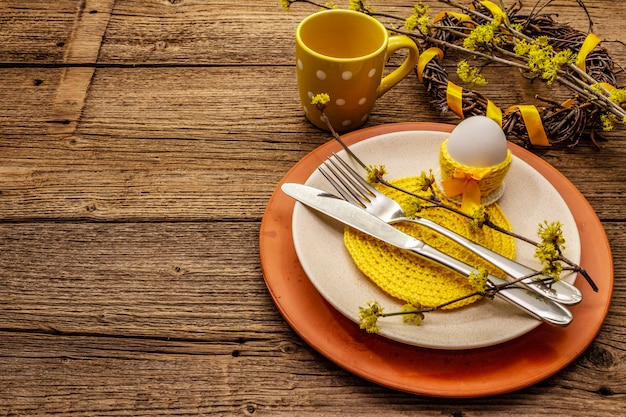 Easter table setting on old wooden background. spring holiday card template. cutlery, crochet napkin, egg, flowering sprigs of dogwood
