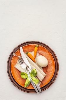 織り目加工の白いパテの背景にイースターテーブルの設定。春のホリデーカードテンプレート。カトラリー、ヴィンテージナプキン、卵、ニンジン、バニー