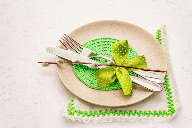 Easter table setting on textured white putty background. spring holiday card template. cutlery, embroidered napkin, bow, willow seals