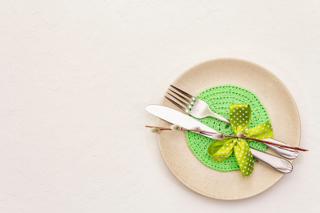 Easter table setting on textured white putty background. spring holiday card template. cutlery, knitted napkin, bow, willow seals