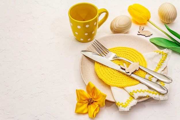 Easter table setting on textured white putty background. spring holiday card template. cutlery, knitted napkin, egg, bunny, tulip, polka dot cup