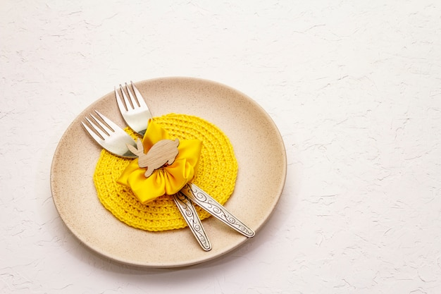 Easter table setting on textured white putty background. spring holiday card template. cutlery, knitted napkin, flower