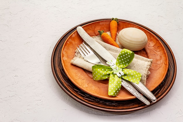 Easter table setting on textured white putty background. spring holiday card template. cutlery, vintage napkin, egg, carrot, bunny