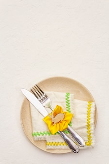 Easter table setting on textured white putty background. spring holiday card template. cutlery, vintage napkin, rabbit, flower