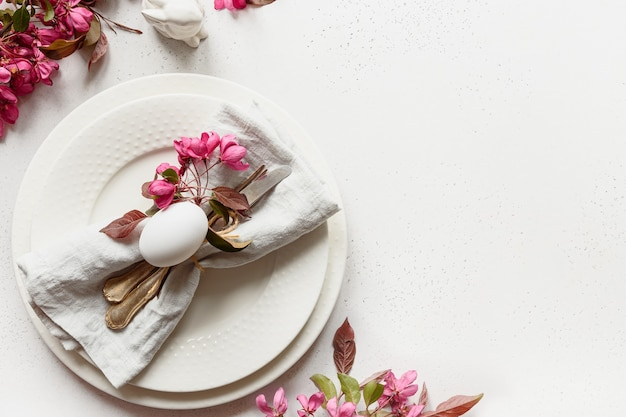 Easter table setting with blooming apple flowers on white table.