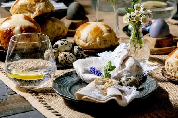 色とチョコレートの卵、ホットクロスバン、花束の花、ナプキンと空のセラミックプレート、テキスタイルテーブルクロスと木製のテーブルにレモネードドリンクのガラスとイースターテーブルの設定。