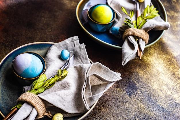 색된 계란과 회양목 잎 부활절 테이블 설정