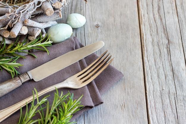 卵とローズマリー灰色の木製のテーブルでイースターテーブルの設定はコピースペースでクローズアップ