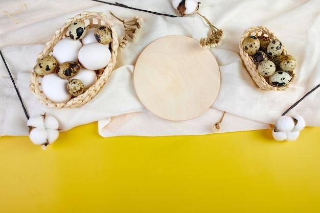 白いテキスタイルリネンのテーブルクロスに卵、綿の花とイースターテーブルの設定。コピースペース、フラットレイ、上面図と休日の背景。