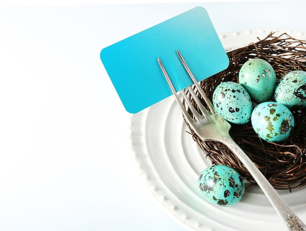 Easter table setting with empty card and easter eggs, on white