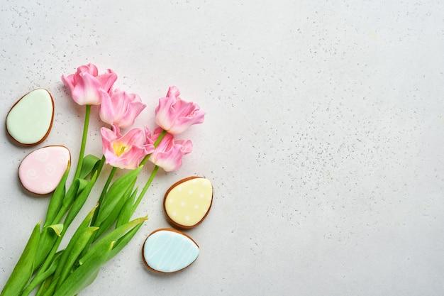 Сервировка пасхального стола с цветочным декором и тарелка с пасхальными пряниками на сером столе