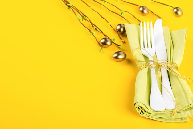Easter table setting with  kitchen cutlery on a bright yellow background