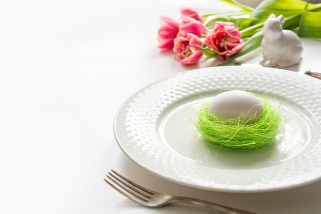 Easter table setting with pink tulip on white. spring romantic dinner.