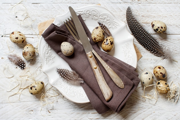 Сервировка пасхального стола перепелиными яйцами и перьями