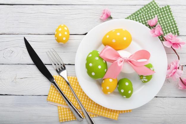 Сервировка пасхального стола с весенними цветами и столовыми приборами. праздники фон