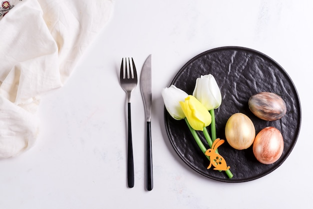 Easter table setting with spring tulips. stone empty plate, cutlery, napkin and golden eggs on stone