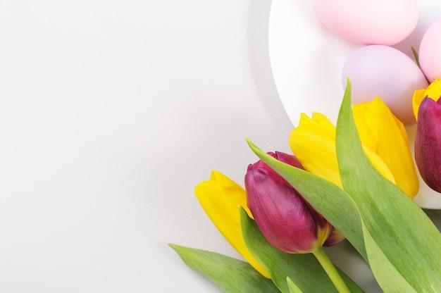Сервировка пасхального стола с желтыми и фиолетовыми тюльпанами на сером фоне. вид сверху