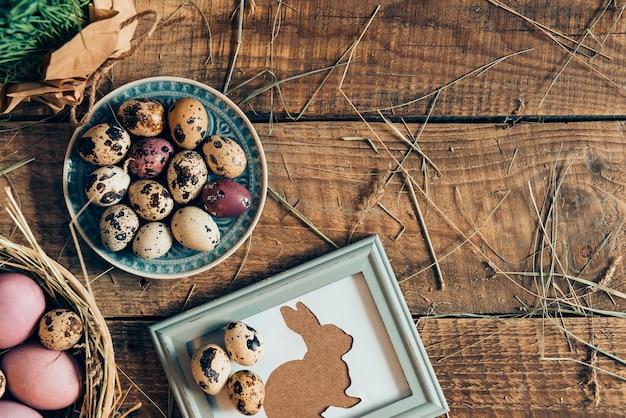イースターテーブル。プレート上のイースターエッグと干し草と木製の素朴なテーブルの上に横たわっている額縁のイースターウサギの上面図