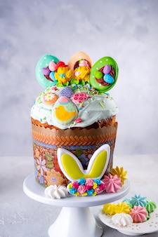 伝統的な休日のイースターケーキが付いたイースターテーブル、p kulichはバニーのアイシング、砂糖漬け、メレンゲで飾られています