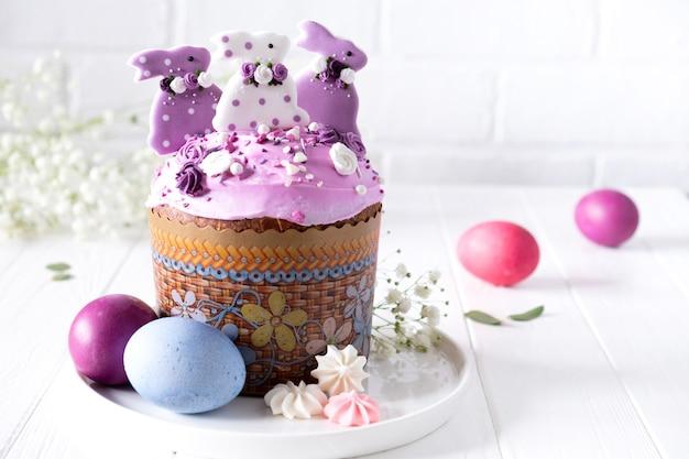 伝統的な休日のイースターケーキ、塗られた卵と花の枝が付いているイースターテーブル Premium写真