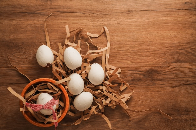 Easter, tied egg with red ribbon in wooden bowl and white eggs on brown paper on wooden table