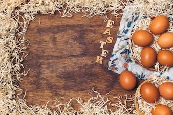 ボード上の見掛け倒しの間に花の咲く材料の上にボウルに鶏の卵の近くのイースタータイトル