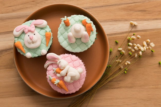 Easter. top view of a beautiful rustic plate with 3 easter cupcakes in bunny head and bunny tail on top.