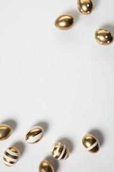 Tradizioni pasquali, uova di colore dorato su sfondo bianco