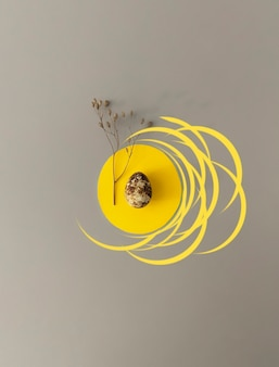 Easter in trendy colors. quail egg with dried flowers on a yellow and gray background with copy space.