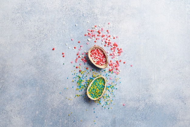 Пасха два половинки шоколадного яйца с конфетой и разбросанной кондитерской заправкой на сером столе. концепция праздничного стола. место для текста.