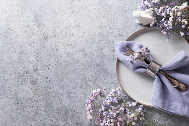 Сервировка стола пасха фиолетовая с зайчиком и праздничным декором на сером столе. вид сверху. место для текста.