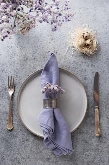 Сервировка стола пасха фиолетовая с белыми яйцами в гнезде и декоре сирени на сером столе. элегантный ужин. вид сверху. вертикальный формат.