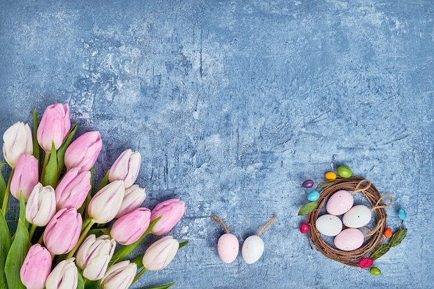 Easter wall with eggs and purple tulips. holiday card with copy space on blue wall, top