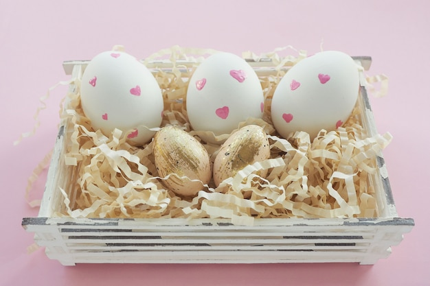 Easter white eggs with pink hearts and beige in black speck and gold strokes in a basket on a pink background.