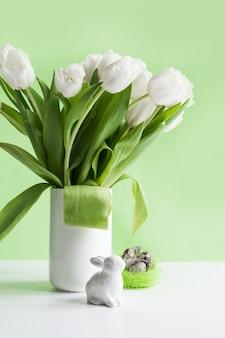 Easter. white tulips in vase, bunny, white eggs on green.