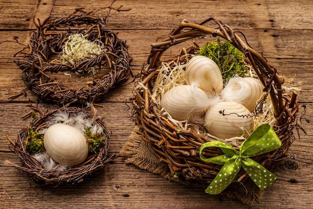 イースターウィッカーバスケット、鳥の巣、花輪。廃棄物ゼロ、diyコンセプト。木製の卵、削りくず、サテンの弓。古いボードの背景