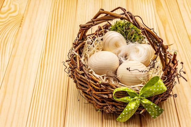 イースター籐のバスケット。廃棄物ゼロ、diyコンセプト。木製の卵、削りくず、サテンの弓。ボードの背景