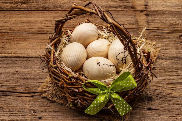 イースター籐のバスケット。廃棄物ゼロ、diyコンセプト。木製の卵、削りくず、サテンの弓。古いボードの背景