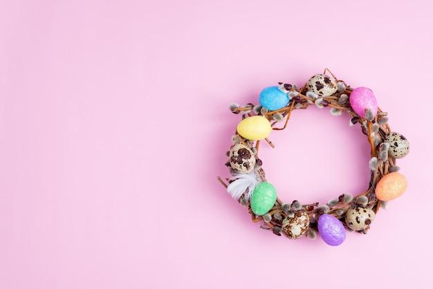 イースター柳の花輪とピンクの背景にカラフルなイースターエッグ。トップビュー、コピースペース