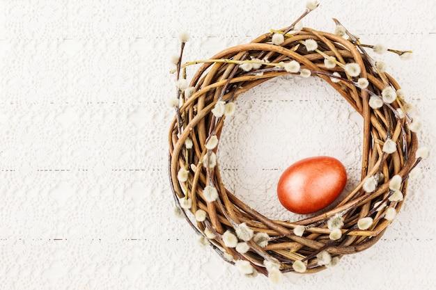 흰색 식탁보에 빨간색 부활절 달걀과 부활절 버드 나무 화 환. 평면도, 복사 공간