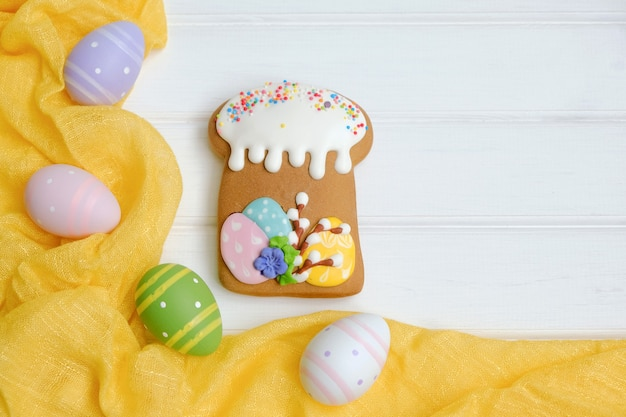 Easter with colorful eggs and traditional cakes over white wooden table.