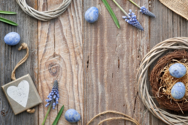 Easter  with eggs, blue hyacinth flowers and  wooden heart, top view on rustic wood, copy-space