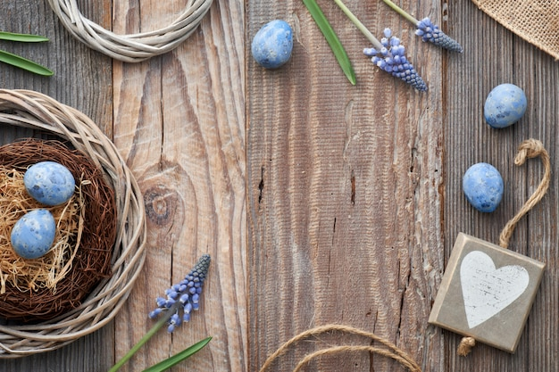 Easter  with eggs, blue hyacinth flowers and  wooden heart, top view on rustic wood,