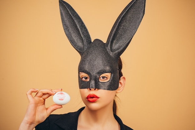 Easter woman. happy easter. lips and easter, lipstick kiss imprint on easter egg. bunny woman. girl with lace bunny ears